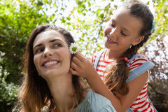 Smiling girl positioning white flower in hair of mother. At backyard Royalty Free Stock Images