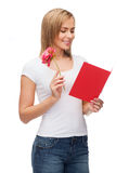 Smiling girl with postcard and flower Royalty Free Stock Photography