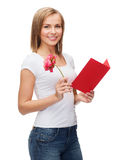 Smiling girl with postcard and flower Royalty Free Stock Images
