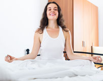 Smiling girl practicing yoga in bed Royalty Free Stock Photo
