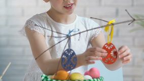 Smiling girl preparing Easter decoration, hanging toy eggs on tree branches, eve stock video footage