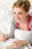 Smiling girl preparing for exams in bed Royalty Free Stock Photo