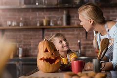 Smiling girl preparing a pumpkin for Halloween with her mother. Halloween is soon. Cheerful delighted little girl preparing a pumpkin for Halloween with her Royalty Free Stock Photography
