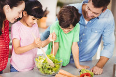 Smiling girl preparing salad with family Royalty Free Stock Images
