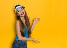 Smiling Girl Presenting. Smiling girl in blue shirt and sun visor presenting something. Three quarter length studio shot on yellow background Stock Photography