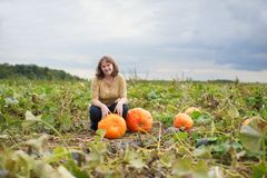 Smiling girl on the pumpkin patch Royalty Free Stock Images