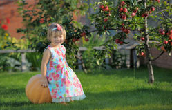 Smiling girl on pumpking over apple tree on a farm. Harvesting time Stock Photo