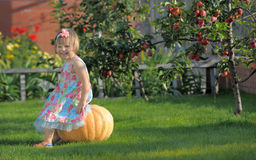 Smiling girl on pumpking. Over apple tree on a farm - harvesting time Stock Photos