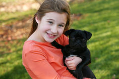 Smiling girl with puppy. Cute little girl holding black pug puppy Royalty Free Stock Images