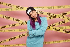 Smiling girl with purple hair tips dressed in blue sweatshirt and black hat stands on the background of pink wall with stock images