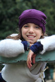 Smiling girl with purple hat. Portrait of a young european girl leaning on the fence Royalty Free Stock Image