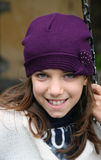 Smiling girl with purple hat. Portrait of a young european girl while holding a chain Stock Photos