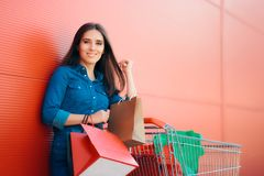 Happy Shopper Woman with Shopping Cart in front of Store. Smiling girl with pushcart and gift bags near shop Royalty Free Stock Images