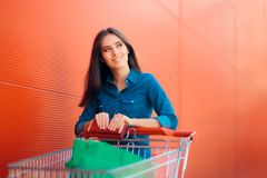 Happy Shopper Woman with Shopping Cart in front of Store. Smiling girl with pushcart and gift bags near shop Royalty Free Stock Photo