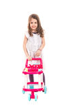 Smiling girl pushing pram toy Stock Photography