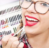 Smiling girl  put the lipstick on the lips Stock Images