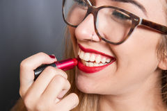 Smiling girl put the lipstick on the lips Stock Photos