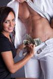 Smiling girl puts dollars in stripper's pants Stock Photos