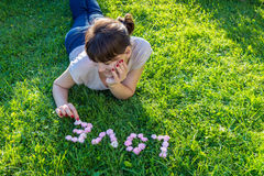 Smiling girl puts the word Love of rose buds on green grass Stock Images