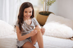 Smiling girl putting band aid on knee at home Stock Images