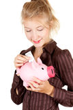 Smiling girl putting five euro in piggy bank Royalty Free Stock Photos