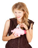 Smiling girl putting five euro in piggy bank Stock Image