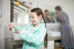 Smiling girl putting toothpaste on toothbrush. In bathroom Royalty Free Stock Images