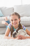 Smiling girl with rabbit lying on rug in living room Stock Images