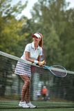 Smiling girl with a racket and ball on the court stock photo