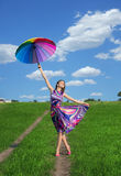 Smiling girl raising her colorful umbrella high Royalty Free Stock Photo