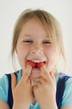 The smiling girl with raspberries in her mouth. The vertical photo of a smiling girl with raspberries in her mouth over light background stock images