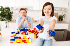 Smiling girl reaching out two construction set pieces Stock Image