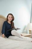 Smiling girl reading in bedroom Stock Photo