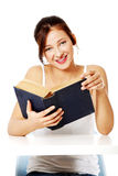 Smiling girl reading a book. Stock Images