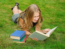 Smiling girl reading book Stock Photo