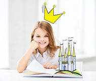 Smiling girl reading fairytales at home. People, children, imagination and fairy tales concept - smiling girl reading book at home with castle and crown doodle Stock Photos
