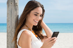 Smiling Girl Reading sms Stock Photo