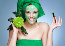 Smiling girl receiving cosmetic facial mask. Photo of pretty girl in green towels and green chrysanthemum flowers on blue background. Grooming himself stock images