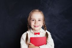 Smiling girl with red book on empty chalkboard background. With copy space. Child portrait royalty free stock images