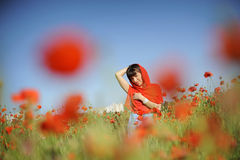 Smiling girl in a red cloth among poppies Stock Images