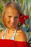 The smiling Girl with red flower. The smiling girl with a red flower in hair Royalty Free Stock Photo