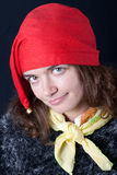 Smiling girl in red gnome hat Royalty Free Stock Photos