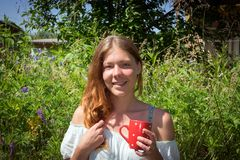 Smiling girl with red hair holds in her hand a red mug with tea on the background of meadow grass stock photo