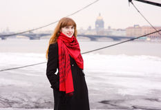 Smiling girl with red hair in the red scarf. Smiling beautiful girl with red hair in the red scarf and black coat Stock Images