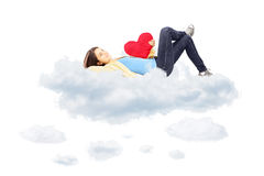 Smiling girl with red heart in her hand lying on clouds Royalty Free Stock Photography