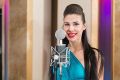 Smiling girl with red lips in room with microphone Stock Photo