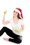 Smiling girl in red Santa Claus hat holds green colored dumbbell Stock Photo