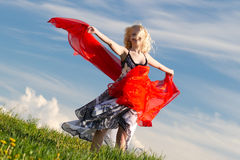 Smiling girl with red scarf. Dancing girl with red scarf on meadow in spring. Tilted version royalty free stock photos