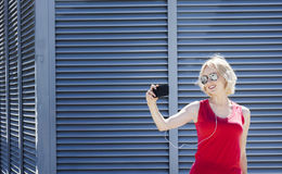 Smiling girl in red shirt taking a photo on smartphone , against metal striped background. Day, outdoor royalty free stock photography
