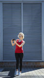 Smiling girl in red shirt taking a photo on smartphone , against metal striped background. Day, outdoor royalty free stock photo